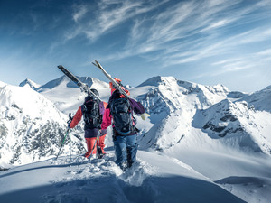 Skiers walking along Austrian mountain promo box